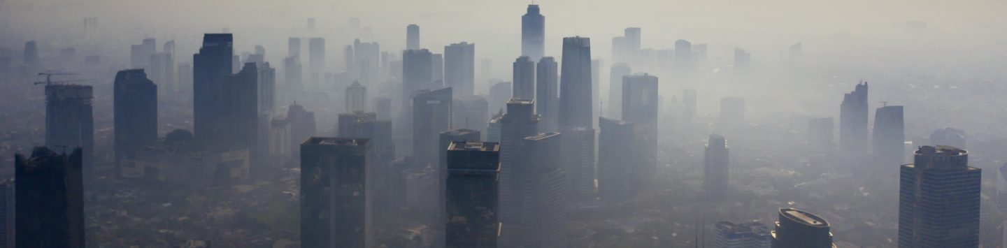 Arial view of skyscrapers surrounded by grey smog.