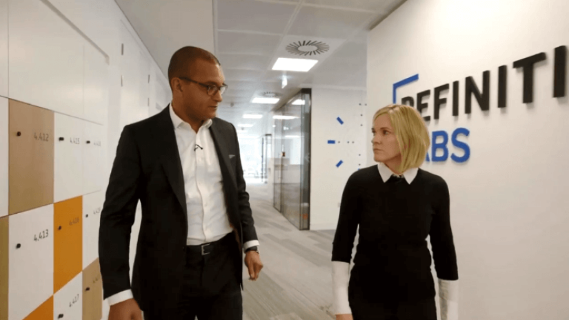 Two Refinitiv employees walking through the company corridors and discussing financial crime